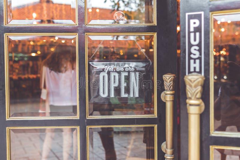 Ouvrez le signe de vintage large par le verre de la fenêtre de magasin l'asie photo stock