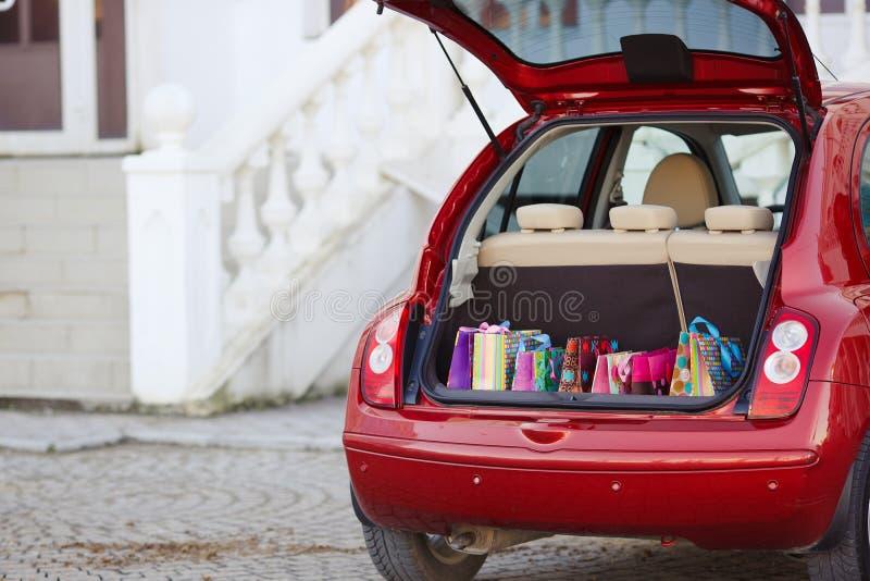 Ouvrez le tronc de la voiture avec des sacs des achats photos stock