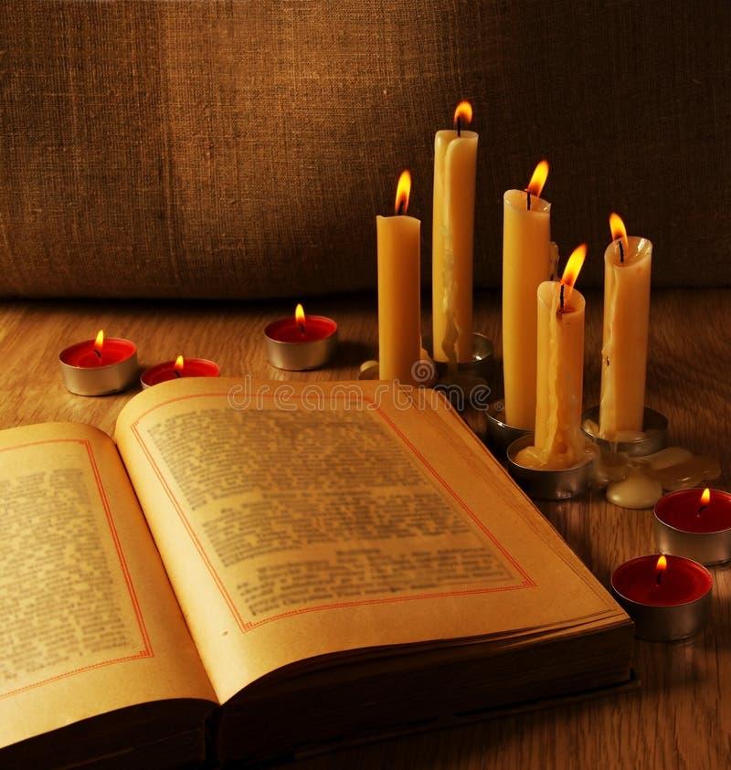 Ouvrez le vieux livre et les bougies brûlantes image stock