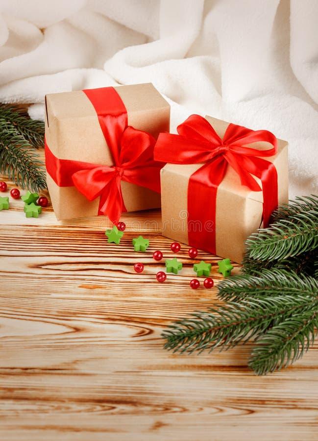 Ouvrez les boîte-cadeau avec le ruban et l'arc rouges, arbre de Noël vert, les décorations, plaid blanc sur le fond en bois Noël  photos libres de droits