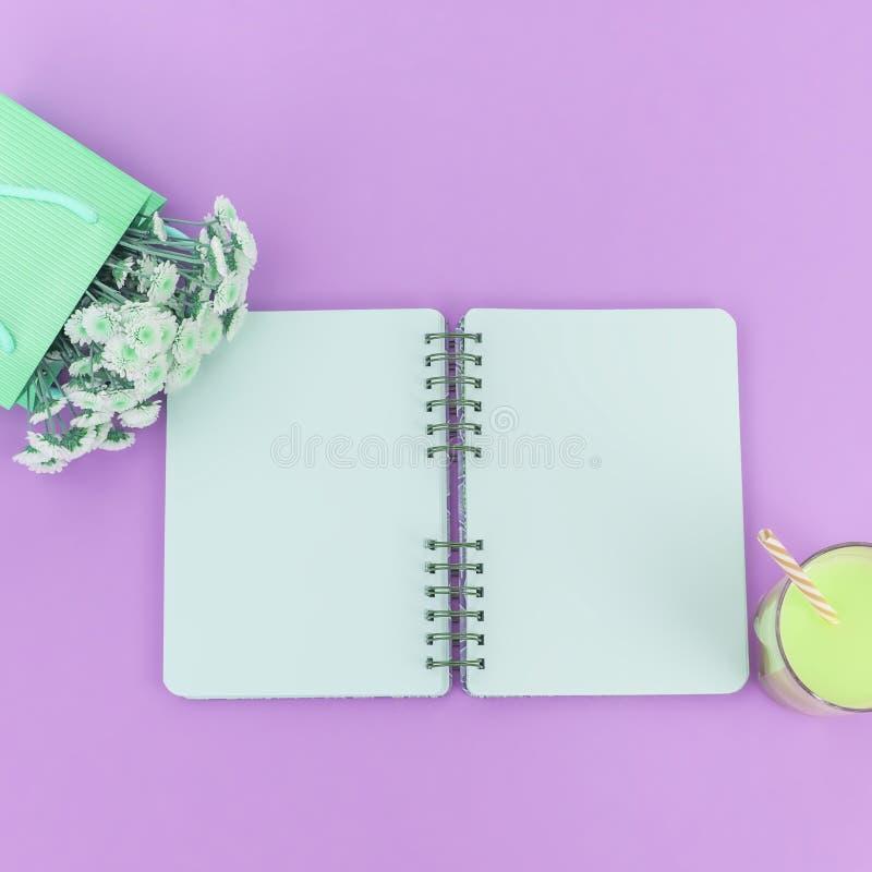 Ouvrez les pages propres de bloc-notes pour écrire un bouquet des fleurs dans un tube de verre en verre de cocktail de sac de pap images stock