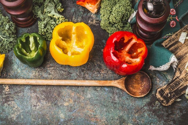 Ouvrez les paprikas vides de paprika pour bourrer de la cuillère en bois sur le fond rustique de table de cuisine photographie stock libre de droits