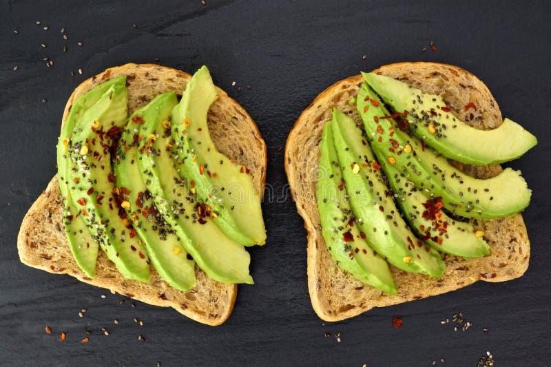 Ouvrez les sandwichs à avocat avec des graines de chia sur l'ardoise foncée photos libres de droits