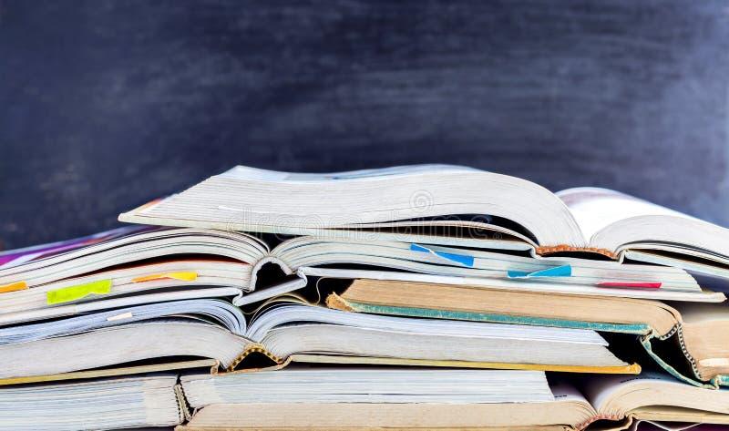 Ouvrez livre cartonné et le manuel empilés sur la table sur le Ba de tableau noir photos libres de droits