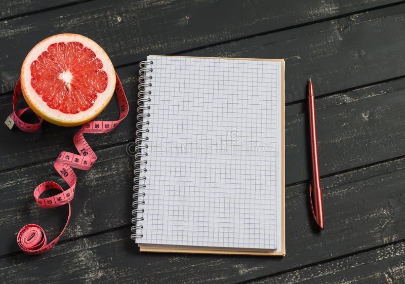 Ouvrez un bloc-notes vide, un pamplemousse, et une bande de mesure sur une table en bois foncée photographie stock libre de droits