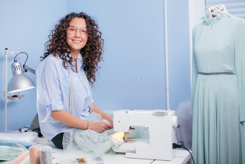 Ouvrière couturière de Cherrful s'asseyant sur le bureau avec des ciseaux à l'intérieur images stock