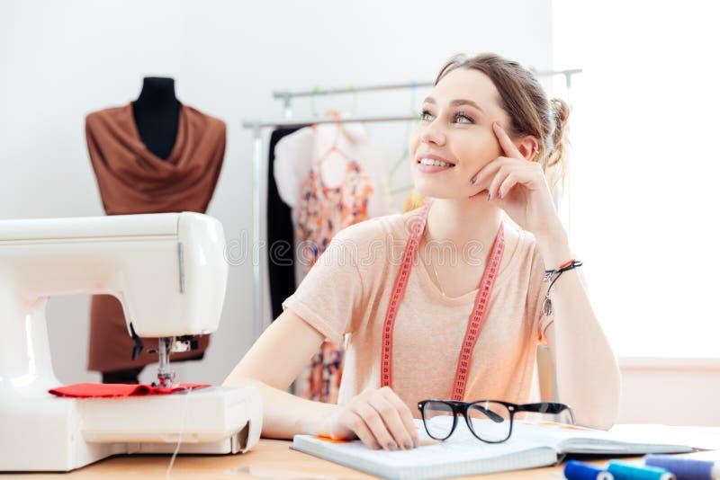 Ouvrière couturière heureuse pensant et travaillant dans le studio photos libres de droits