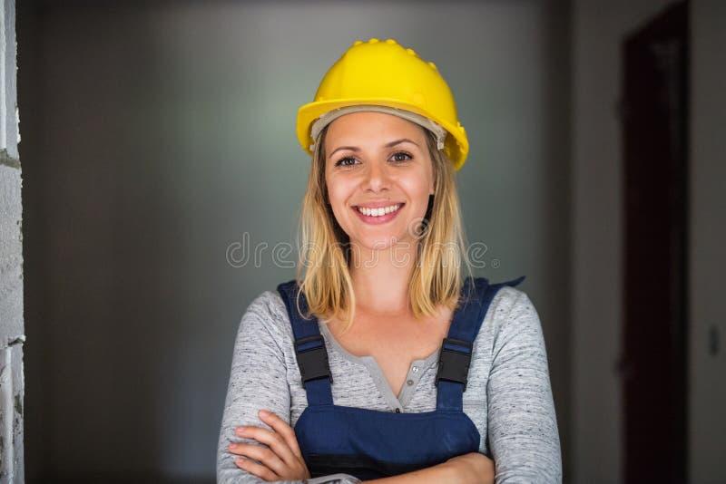 Ouvrière de jeune femme avec un casque jaune sur le chantier de construction photos libres de droits