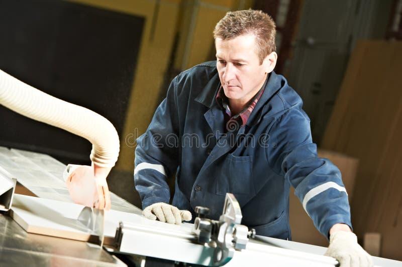 Ouvrier à l'atelier avec la scie de circ images stock