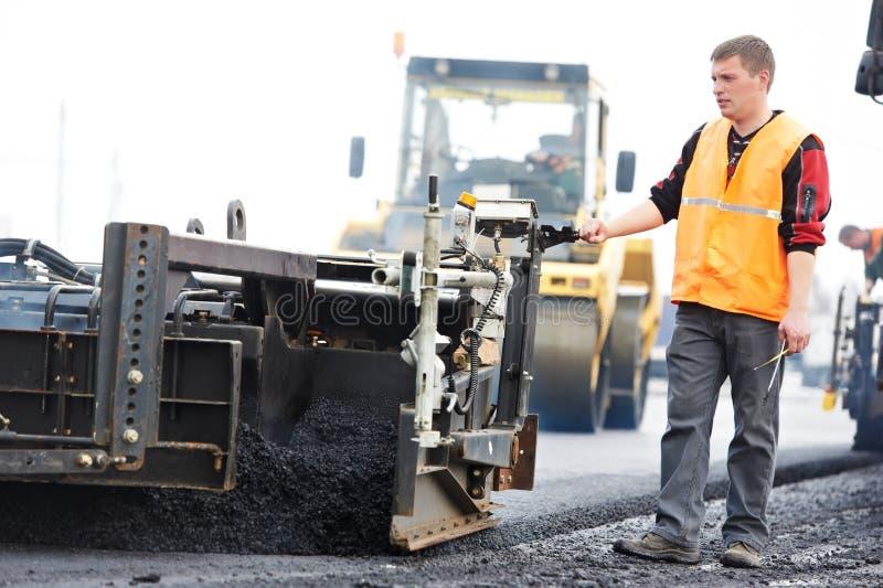 Ouvrier aux travaux de asphaltage photo libre de droits