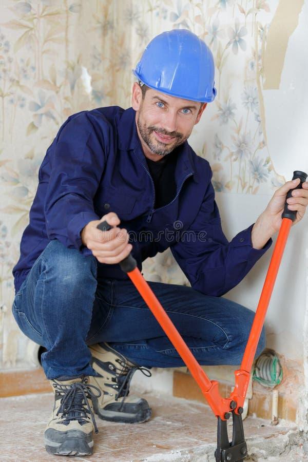 Ouvrier avec la faucheuse de ciseaux au-dessus du fond blanc images libres de droits