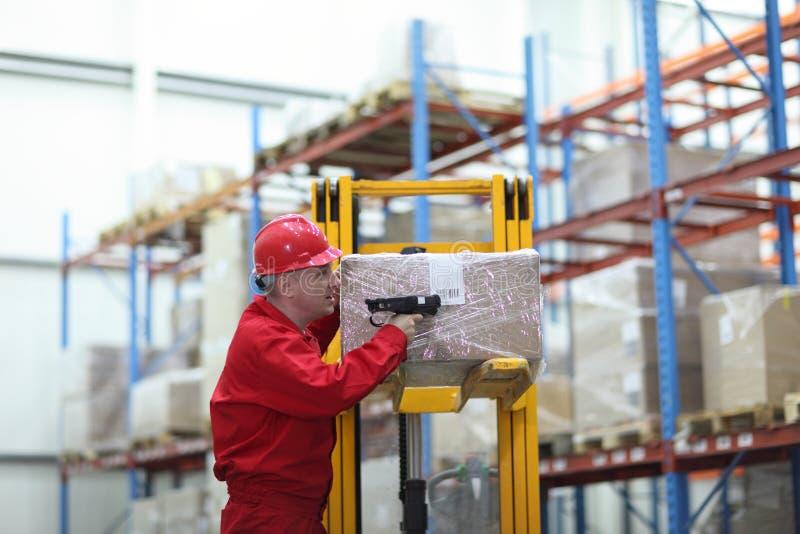 Ouvrier avec le lecteur de code à barres travaillant dans l'entrepôt photos stock