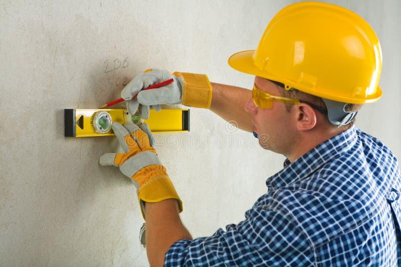 Ouvrier avec le niveau et le crayon de construction photo stock