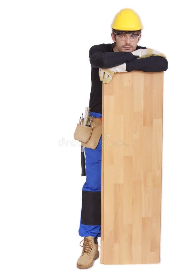 Ouvrier avec le stratifié en bois image stock