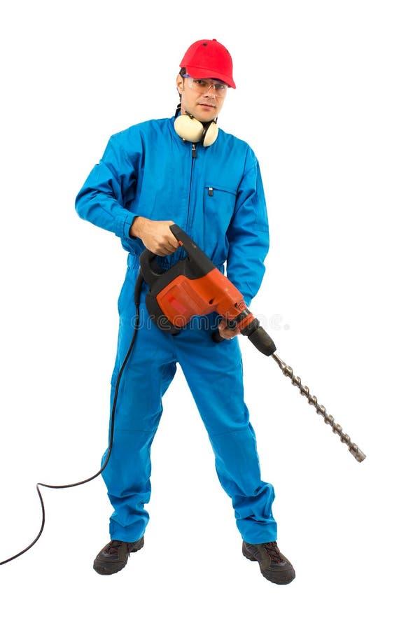 Ouvrier avec un foret de marteau sur le fond blanc image stock