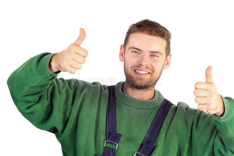 Ouvrier bel dans l'uniforme affichant des pouces vers le haut photo stock
