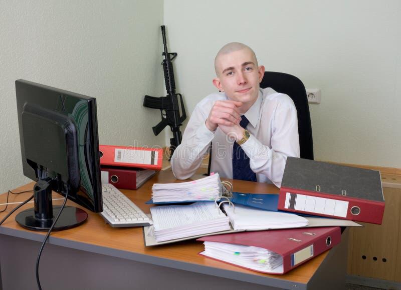Ouvrier content de soi de bureau armé avec un fusil images stock