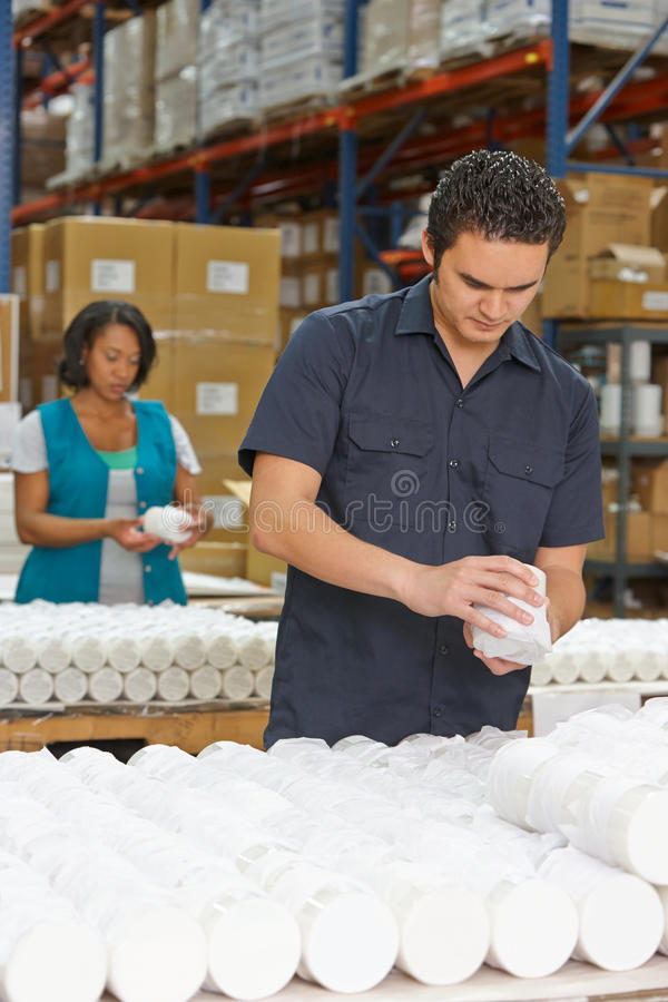 Ouvrier contrôlant des marchandises sur la chaîne de production image libre de droits