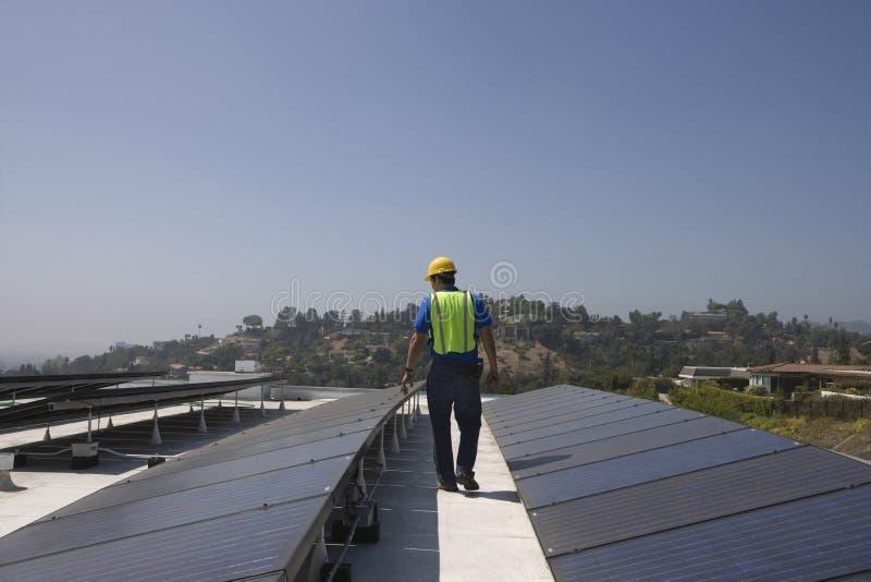 Ouvrier d'entretien inspectant les panneaux solaires sur le dessus de toit photo libre de droits