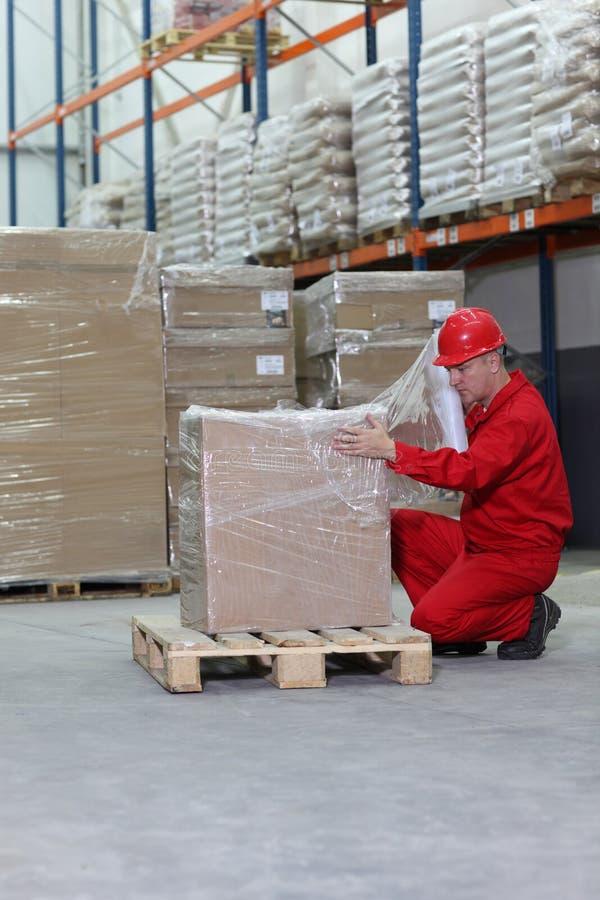 Ouvrier de acroupissement enveloppant le cadre sur la palette photographie stock
