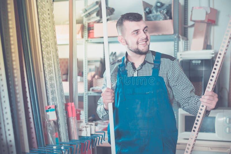 Ouvrier de fabrication dans l'uniforme avec les coins en plastique d'équilibre images libres de droits