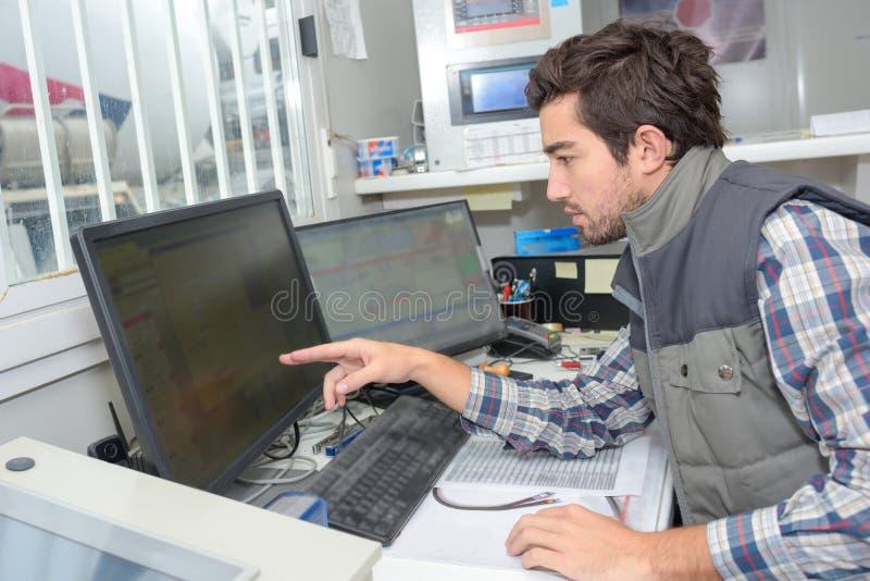 Ouvrier de maintenance du logiciel d'usine image libre de droits