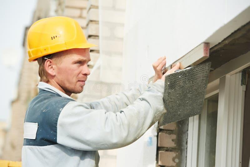 Ouvrier de plâtrier de façade de constructeur avec le niveau photos stock