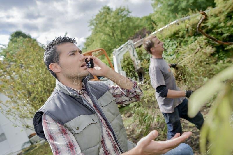 Ouvrier dehors au téléphone image stock