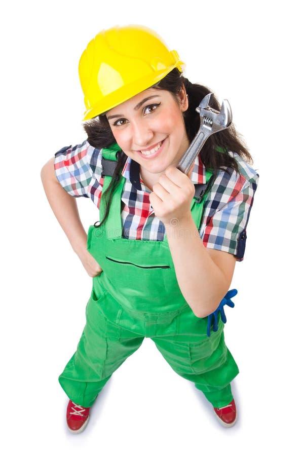 Ouvrier féminin dans des combinaisons vertes tenant la clé photo stock