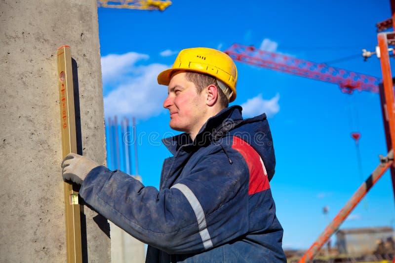 Ouvrier industriel contrôlant le niveau vertical image stock