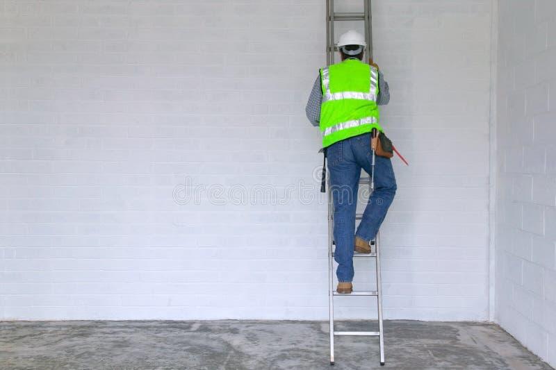 Ouvrier montant une échelle photos stock