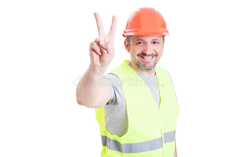 Ouvrier ou constructeur de sourire beau avec le casque montrant le vict image libre de droits