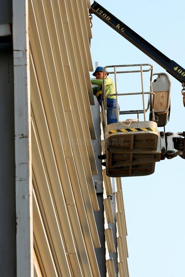 Ouvrier sur la récolteuse de cerise dans le chantier de construction photographie stock