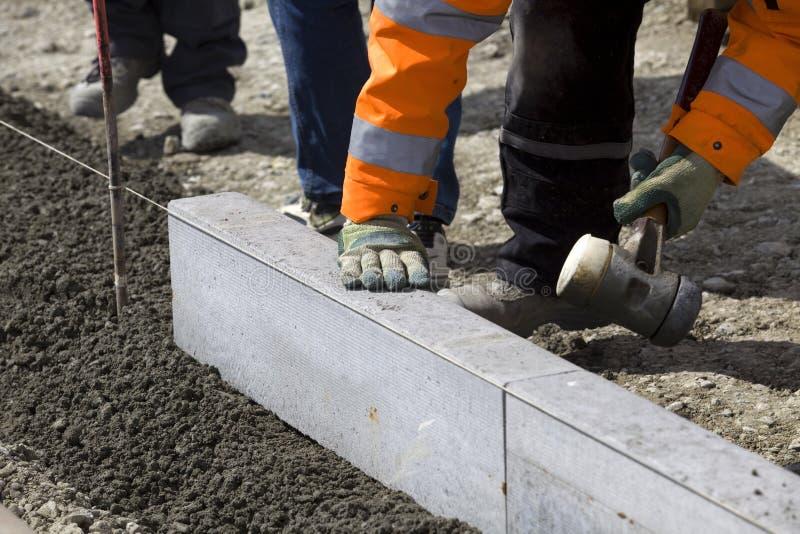 Ouvriers étendant des brames de granit image stock
