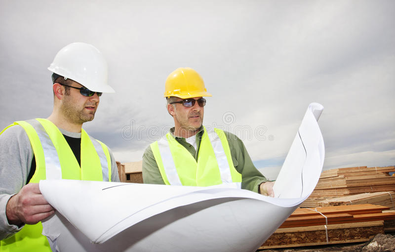 Ouvriers affichant des plans de construction photos libres de droits