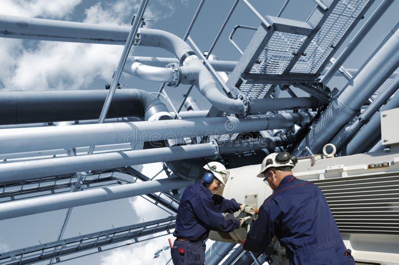 Ouvriers de pétrole et de gaz avec des canalisations d'essence photographie stock