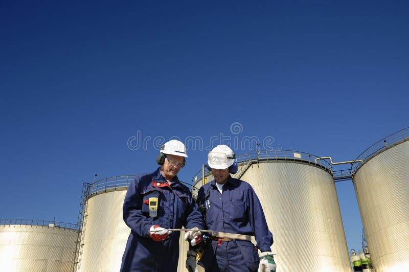 Ouvriers de pétrole et réservoirs de raffinerie photos stock
