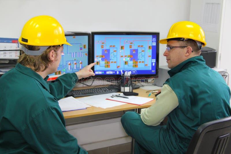 Ouvriers industriels dans la salle de commande photo stock