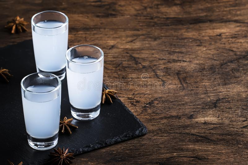 Ouzo - Greek anise brandy, traditional strong alcoholic drink in glasses on the old wooden table, place for text royalty free stock images