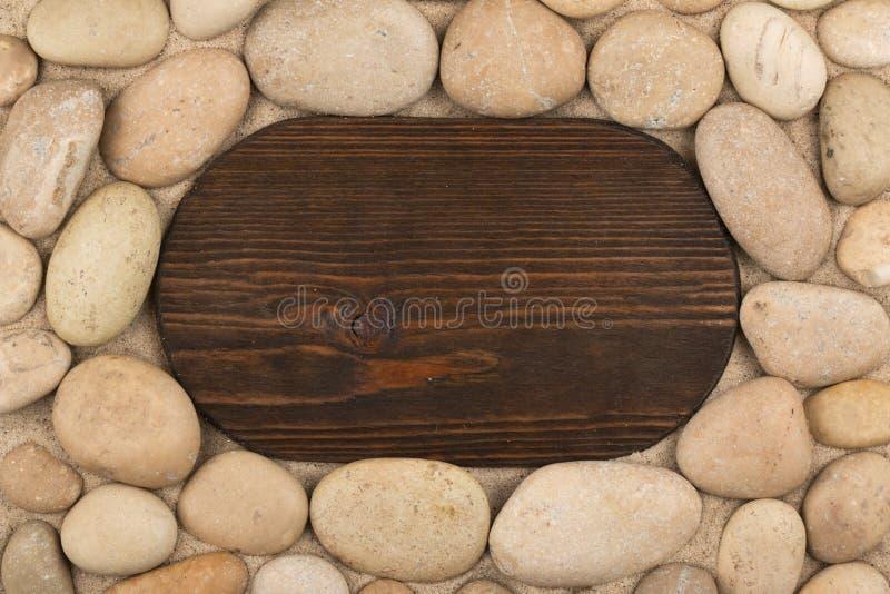 Ovaal klassiek kader van donkere houten en witte stenen in het zand De ruimte van het exemplaar stock fotografie
