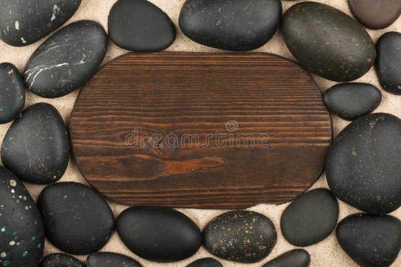 Ovaal klassiek kader van donkere houten en zwarte stenen in het zand De ruimte van het exemplaar stock foto's