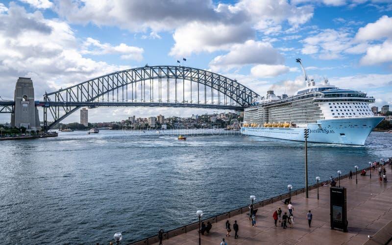 Ovación del barco de cruceros de los mares que deja la opinión circular del muelle y del puente del puerto en Sydney Australia fotografía de archivo libre de regalías