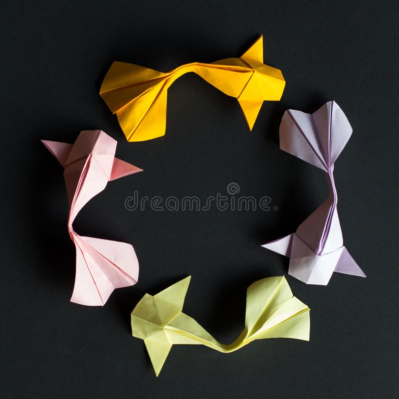 Circular round figure of handmade paper craft origami gold koi carp fishes on black background.Pattern size 1*1, view top. Oval frame figure of handmade paper stock image