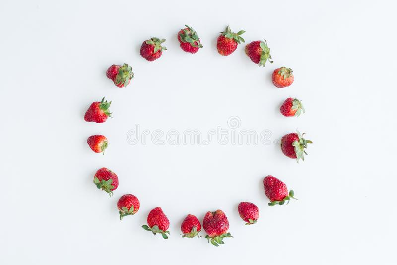 Oval frame of strawberries on white background. Flat lay, top view royalty free stock image
