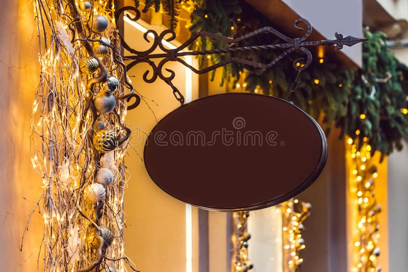Oval metal black forged shop sign in christmas lights and decorations royalty free stock photography