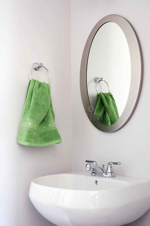 Oval Mirror in Powder Room. A fresh and modern look for a powder room includes a new brushed nickel mirror and a bright green hand towel stock photo