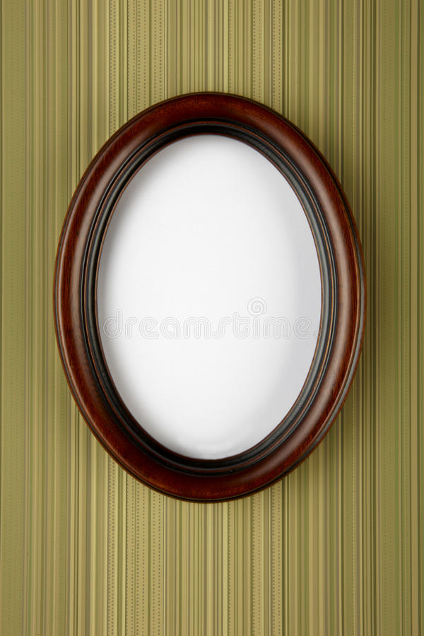 Oval picture frame. Wooden oval picture frame shot on stripped wall paper with space for copy and photograph royalty free stock images