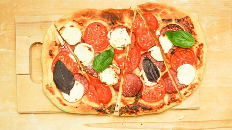 Oval pizza with cheese and sausages, tomatoes and basil stock images