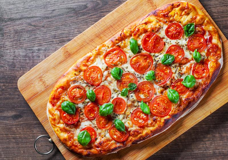Oval Pizza with Mozzarella cheese, Tomatoes, pepper, Spices and Fresh Basil. Italian pizza. Pizza Margherita or Margarita on woode royalty free stock photo