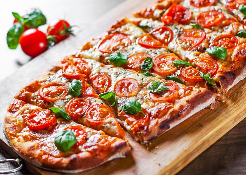 Oval Pizza with Mozzarella cheese, Tomatoes, pepper, Spices and Fresh Basil. Italian pizza. Pizza Margherita or Margarita on woode stock photo
